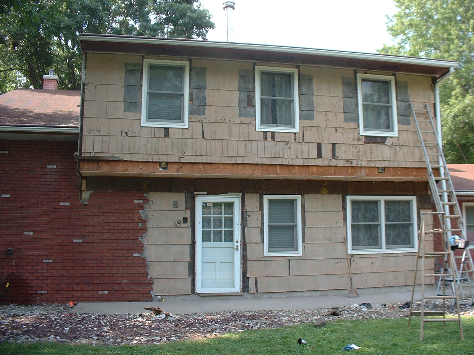 After one day the stucco is half off and the porch roof is down.