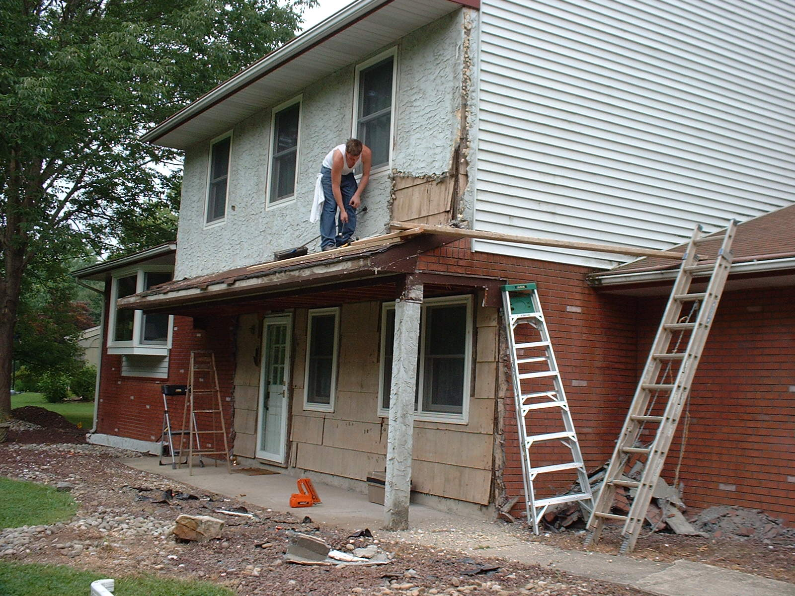 We used the old porch roof as scaffold to take off the stucco on the upper part of the house.